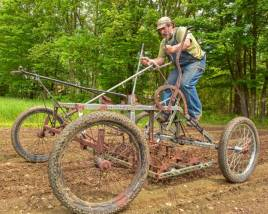 Jeremy Barker-Plotkin, who is a co-owner of Simple Gifts Farm in Amherst, drives a pedal-powered tractor called a Culticycle at the farm, Wednesday.